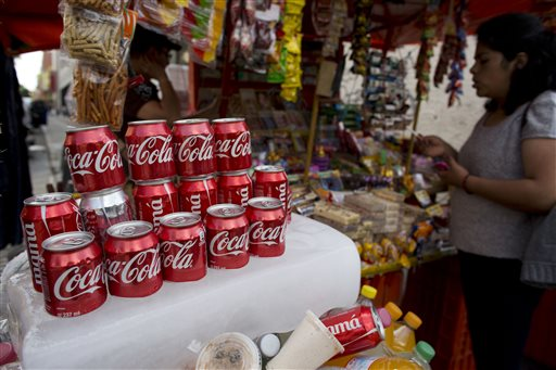 In this Oct. 9, 2014 photo, cans of Coca-Cola sit on an ice block to keep cool at a street vendor's stand in Mexico City. Coca-Cola Co. reports quarterly financial results before the market opens Tuesday, Oct. 21, 2014. (AP Photo/Rebecca Blackwell)