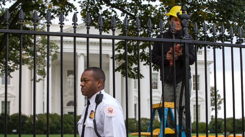 A Secret Service police officer walks outside the White House in Washington, Oct. 23, 2014, as a maintenance worker performs fence repairs as part of a previous fence restoration project. (Evan Vucci/AP Photo)
