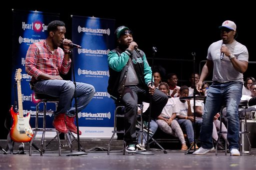 "Shawn Stockman, from left, Wanya Morris, and Nathan Morris of the musical group Boyz II Men, perform at their alma mater, Creative and Performing Arts High School, Tuesday, Oct. 14, 2014, in Philadelphia. The Grammy-winning R&B group, best known for '90s hits like ""I'll Make Love To You"" and ""Motownphilly,"" is set to release their new album, ""Collide,"" next week. (AP Photo/Matt Rourke)"