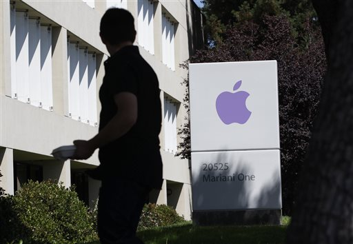 In this Aug. 25, 2011 file photo, an Apple employee walks between Apple buildings at Apple headquarters in Cupertino, Calif. Facebook and Apple, long known for cushy perks such as free meals, laundry service and massages, are among some of Silicon Valley's biggest companies now eyeing reproductive expenses as the next batch of benefits to offer to their employees. (AP Photo/Paul Sakuma, File)