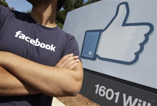 In this Aug. 17, 2012 file photo, a Facebook worker waits for friends to arrive outside of Facebook headquarters in Menlo Park, Calif. Facebook and Apple, long known for cushy perks such as free meals, laundry service and massages, are among some of Silicon Valley's biggest companies now eyeing reproductive expenses as the next batch of benefits to offer to their employees. (AP Photo/Paul Sakuma, File)