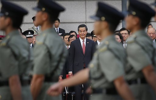 Hong Kong's Chief Executive Leung Chun-ying, center, watches as military personnel march during a flag-raising ceremony on Wednesday, Oct. 1, 2014 in Hong Kong, as thousands of protesters watching from behind police barricades yelled at him to step down. (AP Photo/Wong Maye-E)