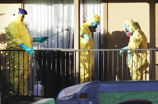 Hazardous material cleaners disinfect their personal protective equipment after working in the apartment where Thomas Eric Duncan, the Ebola patient who traveled from Liberia to Dallas, stayed last week, Oct. 5, in Dallas. A homeless man being sought because of possible contact with the lone U.S. Ebola patient was found in Texas after several hours of searching, authorities said.(AP Photo)