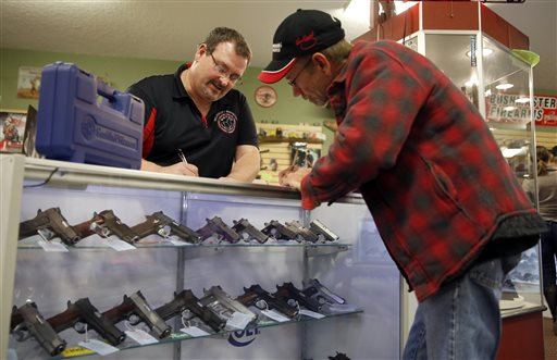 In this Saturday, Nov. 15, 2014 photo, Steven King, left, fills out paperwork while selling a handgun to Dave Benne at Metro Shooting Supplies, in Bridgeton, Mo. Benne, a resident of Florissant, Mo., near Ferguson, said the upcoming grand jury decision on whether to indict police officer Darren Wilson prompted the purchase of his first gun. (AP Photo/Jeff Roberson)