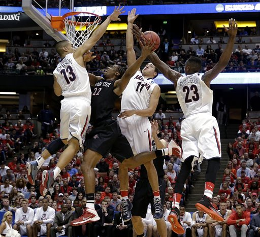 In this March 27, 2014, file photo, San Diego State forward Josh Davis (22) shoots between Arizona guard Nick Johnson (13), Aaron Gordon (11) and Rondae Hollis-Jefferson (23) during the first half in a regional semifinal of the NCAA men's college basketball tournament in Anaheim, Calif. This season, there are fewer star players, putting the focus on the team instead of individual players. (AP Photo/Jae C. Hong, File)
