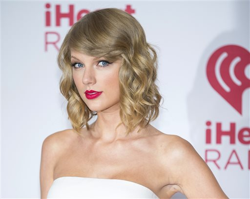 """In this Sept. 19, 2014 file photo, Taylor Swift arrives at the iHeart Radio Music Festival in Las Vegas. The music streaming service Spotify is no longer offering Swift songs at her request, setting up a battle between the industry's most popular artist and the leading purveyor of a new music distribution system. Spotify, which pulled Swift's songs on Monday, Nov. 3, 2014, said that """"we hope she'll change her mind and join us in building a new music economy that works for everyone.""""  (Photo by Andrew Estey/Invision/AP, File)"""