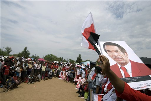 Supporters of the leader of the ruling Botswana Democratic Party, President Seretse Khama Ian Khama wave his portrait on election poster, right, and cheer during an election rally in Gaberone, Botswana Thursday Oct. 15, 2009, on the eve of the country's general election. Botswana's governing party is expected to prevail over a divided opposition in Friday's elections despite added pressure on leaders in the world's largest diamond-producing country amid the global recession. The party has been in power since Botswana won independence from Britain in 1966. (AP Photo/Monirul Bhuiyan)