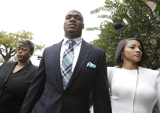 Minnesota Vikings running back Adrian Peterson arrives at the courthouse with his wife Ashley Brown Peterson, right, for an appearance Tuesday, Nov. 4, 2014, in Conroe, Texas. A judge presiding over Adrian Peterson's child abuse case may consider whether the Vikings star should be arrested for allegedly smoking marijuana while out on bond. (AP Photo/Pat Sullivan)