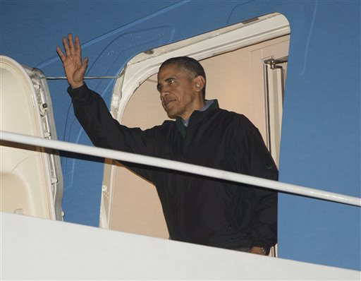 President Barack Obama waves from Air Force One as he arrives from Brisbane, Australia, by way of Hawaii, Sunday, Nov. 16, 2014, at Andrews Air Force Base, Md. (AP Photo/Pablo Martinez Monsivais)