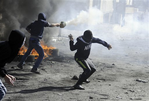 In this Nov. 7, 2014 file photo Palestinians throw rocks and shoot fireworks during clashes with Israeli border police, as Israeli police limited the access to Al-Aqsa Mosque in Jerusalem. 2014 has been a difficult year for Israelis and Palestinians, with the failure of peace talks and a string of violent incidents that shows no signs of ending. (AP Photo/Mahmoud Illean, File)