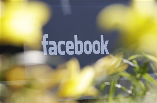 This Friday, May 18, 2012, file photo shows Facebook's headquarters behind flowers in Menlo Park, Calif. Facebook is stepping up its efforts to fight Ebola by adding a button designed to make it easier for its users to donate to charities battling the disease. (AP Photo/Paul Sakuma, File)