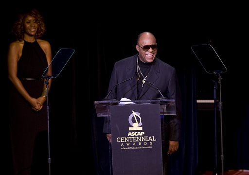 Stevie Wonder speaks as his partner Tomeeka Robyn Bracy listens at the 2014 ASCAP Centennial Awards, benefiting the ASCAP Foundation and its music education, talent development and humanitarian activities, at the Waldorf-Astoria on Monday, Nov. 17, 2014, in New York. (Photo by Stephen Chernin/Invision/AP)