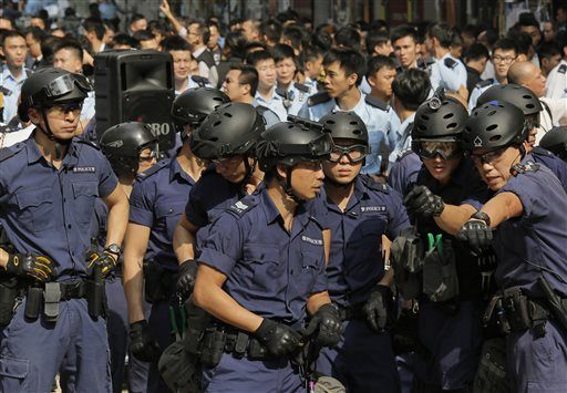 Police officers discuss before taking action as they clear further rows of metal barricades while others tear down tents and canopies and carry away other obstructions after bailiffs issued a warning to the crowd that they would start enforcing the court-ordered clearance at an occupied area in Mong Kok district of Hong Kong Wednesday, Nov. 26, 2014. Hong Kong authorities cleared street barricades from the pro-democracy protest camp in the volatile Mong Kok district for a second day Wednesday after a night of clashes in which police arrested 116 people. (AP Photo/Vincent Yu)