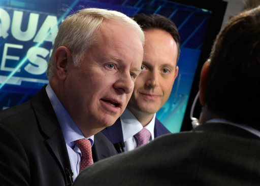 """In this Nov. 17, 2014 file photo, Allergan CEO David Pyott, left, and Actavis CEO Brenton Saunders, are interviewed on the floor of the New York Stock Exchange. Pyott is set to rake in an estimated $100 million in """"golden parachute"""" payments, according to a study done by pay-tracking firm Equilar at the request of The Associated Press. (AP Photo/Richard Drew)"""