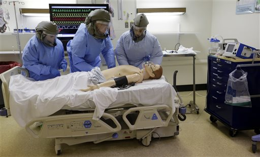 Medical workers wearing protective equipment surround a simulated patient during a demonstration for media members on their training for working with possible Ebola patients, Thursday, Nov. 6, 2014, at Madigan Army Medical Center on Joint Base Lewis McChord, near Tacoma, Wash. Madigan providers and nurses have been training to perform clinical skills, including inserting IVs, obtaining blood samples for testing and conducting ultrasounds while dressed in powered air purifying respirators, impermeable suits and multiple layers of gloves. The clinically-focused exercises use realistic patient simulators that speak through microphones and can express simulated bodily fluids. (AP Photo/Elaine Thompson)