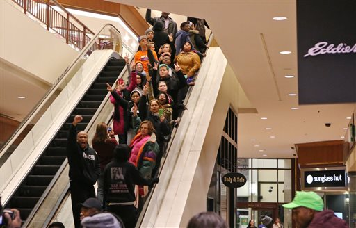 Protesters of the grand jury decision in the Michael Brown shooting chant slogans at the St. Louis Galleria mall on Wednesday evening, Nov. 26, 2014, in Richmond Heights, Mo. They stayed in the mall for about 15 minutes and then left peacefully without confrontation with a large police presence. (AP Photo/St. Louis Post-Dispatch, J.B. Forbres)