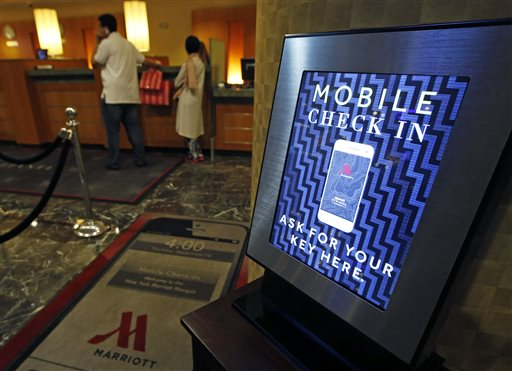 In this Oct. 14, 2014 photo, a mobile check-in option is offered for travelers at the main check-in counter at the Marriott Marquis Times Square hotel in New York. Marriott International launched the ability to check in through its app at 330 North American hotels last year. By the end of this year, the program will be live at all 4,000 hotels worldwide. (AP Photo/Kathy Willens)