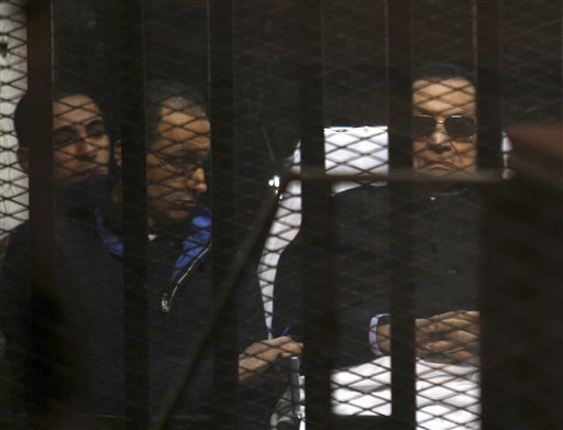 Ousted Egyptian President Hosni Mubarak, 86, lies on a gurney, next to his son Gamal, second left, in the defendants cage, during a court hearing in Cairo, Egypt, Saturday, Nov. 29, 2014. An Egyptian court on Saturday dismissed murder charges against former president Hosni Mubarak in connection with the killing of protesters in the 2011 uprising that ended his nearly three-decade reign. Saturday's verdict concludes Mubarak's retrial along with his two sons, his security chief and six top security commanders, who were all acquitted. (AP Photo/Tarek el-Gabbas)