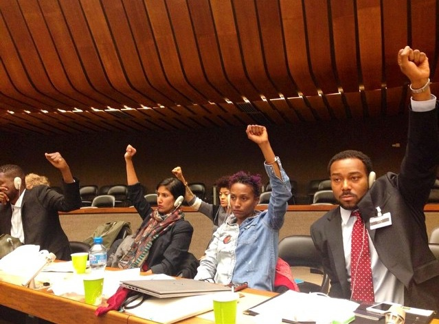 During a hearing, the Ferguson to Geneva, delegation lifts their fists in solidarity with the youth-led We Charge Genocide delegation from Chicago (not pictured). From right to left, Justin Hansford, Tara Thompson, and Meena Jagannath. (Charles Wade/Ferguson to Geneva)
