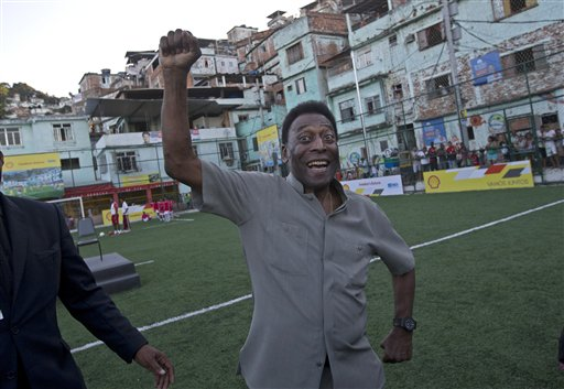 In this Sept. 10, 2014 file photo, Brazilian soccer great Pele pumps his fist in the air while he poses for photos during the inauguration of a soccer pitch to be powered by players' footsteps, at the Morro da Mineira favela, in Rio de Janeiro, Brazil. Pele remains in good condition after undergoing surgery to remove kidney stones, the Albert Einstein Hospital in Sao Paulo said in a statement released Friday, Nov. 14, 2014. (AP Photo/Silvia Izquierdo, File)