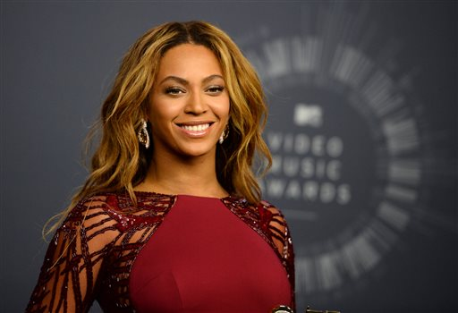 """In this Aug. 24, 2014 file photo, Beyonce poses in the press room at the MTV Video Music Awards at The Forum in Inglewood, Calif. British newcomer Sam Smith and Beyonce - the most nominated female in Grammy history - are the current leaders at the Grammy Awards with five each. Smith and Beyonce will likely earn nominations for album of the year, the top award, when The Recording Academy announces the nominees Friday night, Dec. 5, 2014, on """"A Very GRAMMY Christmas"""" (9 p.m., CBS). (Photo by Jordan Strauss/Invision/AP, File)"""