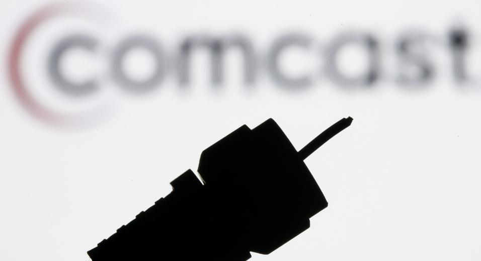 In this July 30, 2008 file photo illustration, a silhouetted coaxial cable with the Comcast Corp. logo in the background is seen in Philadelphia. (AP Photo/Matt Rourke, file)