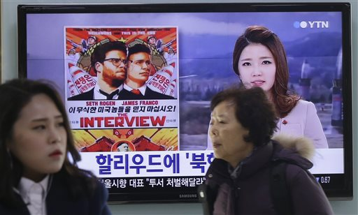 """In this Monday, Dec. 22, 2014, file photo, people walk past a TV screen showing a poster of Sony Picture's """"The Interview"""" in a news report,  at the Seoul Railway Station in Seoul, South Korea. A South Korean activist said Wednesday, Dec. 31, 2014, that he will launch balloons carrying DVDs of Sony's """"The Interview"""" toward North Korea to try to break down a personality cult built around the country's leader Kim Jong Un. (AP Photo/Ahn Young-joon, File)"""