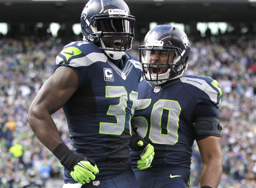 Seattle Seahawks' Kam Chancellor, left, and K.J. Wright, right, celebrate a play against the St. Louis Rams in the second half of an NFL football game, Sunday, Dec. 28, 2014, in Seattle. (AP Photo/John Froschauer)