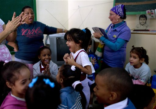 "Students and teachers celebrate after listening to a live, nationally broadcast speech by Cuba's President Raul Castro about the country's restoration of relations with the United States, at a school in Havana, Cuba, Wednesday, Dec. 17, 2014. Castro said profound differences remain between Cuba and the U.S. in areas such as human rights, foreign policy and questions of sovereignty, but that the countries have to learn to live with their differences ""in a civilized manner."" (AP Photo/Ramon Espinosa)"