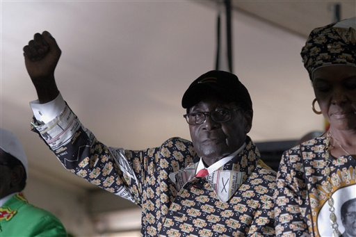 "Zimbabwean President Robert Mugabe gestures as he greets the crowd upon arrival on the last day of the Zanu PF  6th National Congress, in Harare, Sat, Dec. 6, 2014. Zimbabwe's vice president was a rebel commander known as ""Spill Blood"" during the war against white rulers and, at the age of 25, became the youngest Cabinet minister after independence. Now she is a political pariah, accused of plotting the downfall of President Robert Mugabe with the help of nocturnal sorcery. (AP Photo/Tsvangirayi Mukwazhi)"