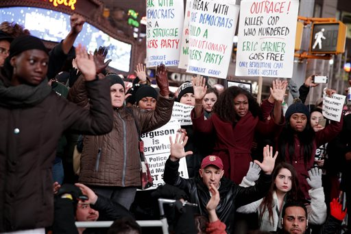 People participate in a protest in response to the grand jury's decision in the Eric Garner case in Times Square in New York, Wednesday, Dec. 3, 2014. The grand jury cleared the white New York City police officer Wednesday in the videotaped chokehold death of Garner, an unarmed black man, who had been stopped on suspicion of selling loose, untaxed cigarettes, a lawyer for the victim's family said. (AP Photo/Seth Wenig)