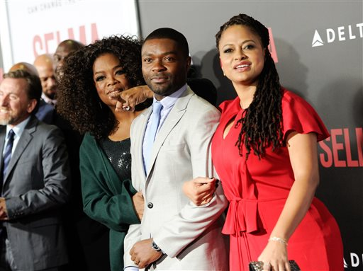 "Producer Oprah Winfrey, left, poses with actors David Oyelowo and Carmen Ejogo at the premiere of ""Selma"" at the Ziegfeld Theatre on Sunday, Dec. 14, 2014, in New York. (Photo by Evan Agostini/Invision/AP)"