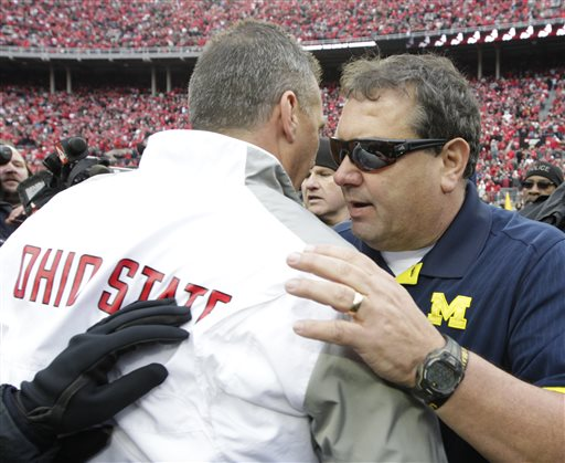 Michigan head coach Brady Hoke, right, shakes hands with Ohio State head coach Urban Meyer after Ohio State beat Michigan in an NCAA college football game Saturday, Nov. 29, 2014, in Columbus, Ohio. Ohio State beat Michigan 42-28. (AP Photo/Jay LaPrete)