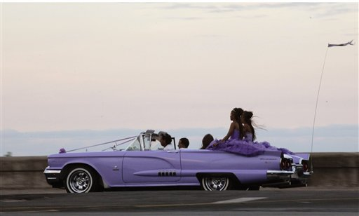 In this Dec. 19, 2014 photo, girls ride on the back of an American vintage car along the Malecon during a 15th birthday celebration in Havana, Cuba.  U.S. car sales have been banned in Cuba since 1959. Cubans have been have been forced to patch together Fords, Chevrolets and Chryslers that date back to before Fidel Castro's revolution which can make it appear like the country is stuck in a 1950s time warp. Since the Communist economic system isn't likely to change soon, many of those cars will have to stay on the road for years. (AP Photo/Desmond Boylan)