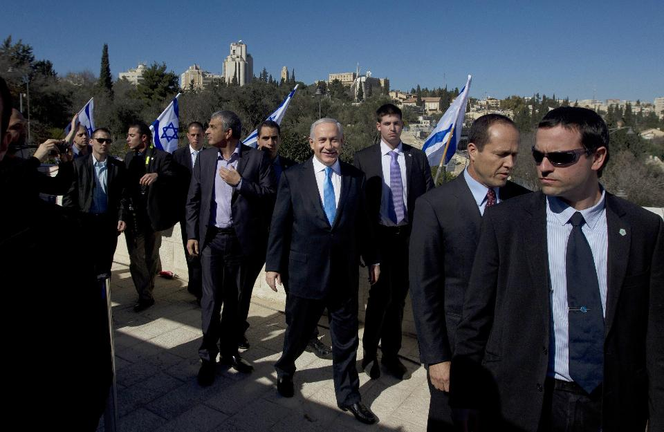 In this Jan. 21, 2013 Israeli Prime Minister Benjamin Netanyahu, center, is surrounded by bodyguards as he arrives with Jerusalem Mayor Nir Barkat, second right, and Likud party member Moshe Kahlon, left, to brief the media in Jerusalem. Even before Israel's hastily called election campaign kicks into high gear, a former ally of Prime Minister Benjamin Netanyahu is shaping up to be this round's wildcard and potential kingmaker. Kahlon was the most popular Likud minister in Netanyahu's previous government, drawing wide appeal for both his working-class character and for pushing daring reforms. But prior to the 2013 election he abruptly quit politics over differences with Netanyahu. Now he's back with a new centrist party that focuses on Israel's economic woes and could tip the scales in favor of those seeking to topple the longtime Israeli leader. (AP Photo/Sebastian Scheiner, File)