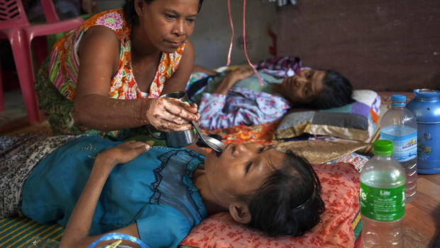 In this photo taken Sunday, Nov. 30, 2014, a woman gives water to an HIV patient receiving treatments at an HIV/AIDS Care Center on the outskirts of Yangon, Myanmar. (Khin Maung Win/AP Photo)