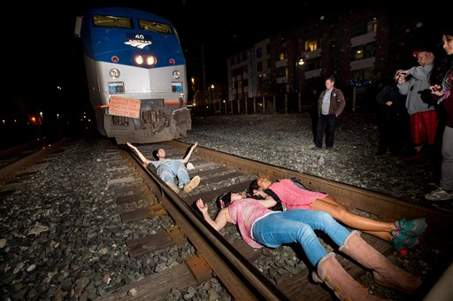 Protesters block an Amtrak train in Berkeley, Calif., on Monday, Dec. 8, 2014. Hundreds of people marched through Berkeley for a third night, blocking an interstate highway and stopping the train as activists rallied against grand jury decisions not to indict white police officers in the deaths of two unarmed black men. (AP Photo/Noah Berger)