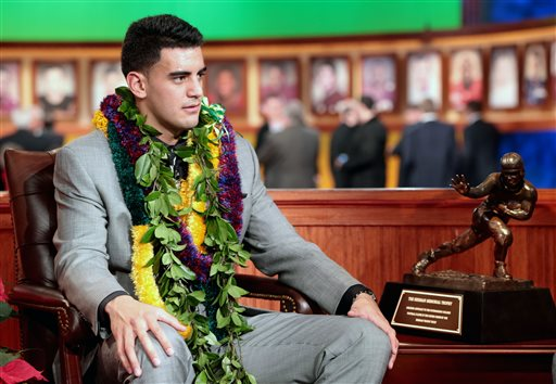 In this photo provided by the Heisman Trust, Oregon quarterback Marcus Mariota  sits next to the Heisman Trophy after being named college football's best player during the Heisman Trophy presentation in New York on Saturday, Dec. 13, 2013. (AP Photo/Heisman Trust, Kelly Kline)