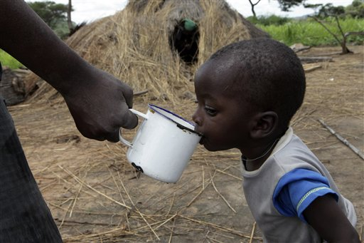 In this photo taken Thursday, Jan. 15, 2015, a child drinks water outside his grass-hut dwelling, destroyed by the police, at Manzou Farm in Mazoe, north of Harare. It has been reported by that police officers destroyed the thatch huts on Manzou farm, a grassy piece of land with scattered acacia trees and overlooked by wooded hills in Mazowe, a prime farming district 40 kilometers (25 miles) north of the capital Harare.  The police told the source and other protesting tenants that the land was earmarked for Grace Mugabe. (AP Photo/Tsvangirayi Mukwazhi)