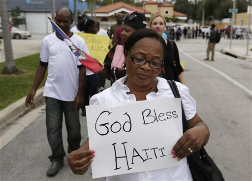 Marilia Lexsidor walks during a silent march commemorating the fifth anniversary of a devastating earthquake that struck Haiti, Monday, Jan. 12, 2015, in the Little Haiti neighborhood of Miami. The 7.0 magnitude earthquake struck in 2010, and the Haitian government has said more than 300,000 people were killed. The exact toll is unknown because there was no systematic effort to count bodies among the chaos and destruction. (AP Photo/Lynne Sladky)
