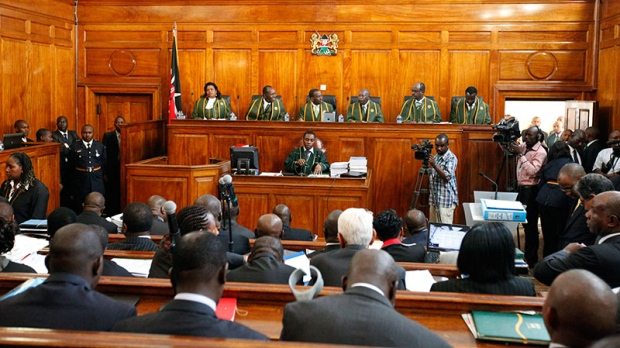 The six Supreme Court judges, led by Chief Justice Willy Mutunga, seated third left, listen to the petition that Kenya's Prime Minister Raila Odinga has filed against president-elect Uhuru Kenyatta at the Supreme Courts in Nairobi, Kenya, Monday, March 25, 2013. (AP/Sayyid Azim)
