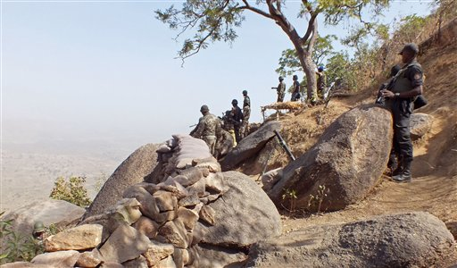 In this photo taken on Thursday, Feb. 19, 2015, Cameroon soldiers stand guard at a lookout post as they take part in operations against the Islamic extremist group Boko Haram near the village of Mabass, Cameroon. Cameroon officials say prisons are overcrowded with suspected Islamic extremists whose insurgency has spilled from Nigeria. (AP Photo/Edwin Kindzeka Moki)
