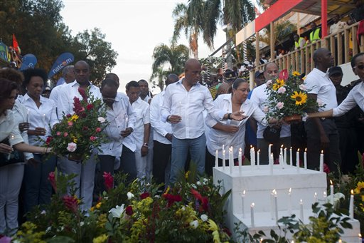 Haiti's new Prime Minister Evans Paul, left center, Haiti's President Michel Martelly, center, and first lady Sophia Martelly, lead a vigil at the site of a high-voltage wires' accident that left at least 16 people dead, in Port-au-Prince, Haiti, Tuesday, Feb. 17, 2015. The accident occurred early Tuesday as thousands of people filled the downtown streets for Carnival celebrations. Officials say a man on top of a musical group's float was shocked by high-voltage wires above the street, setting off a panic in which dozens of people were trampled. ( AP Photo/Dieu Nalio Chery)