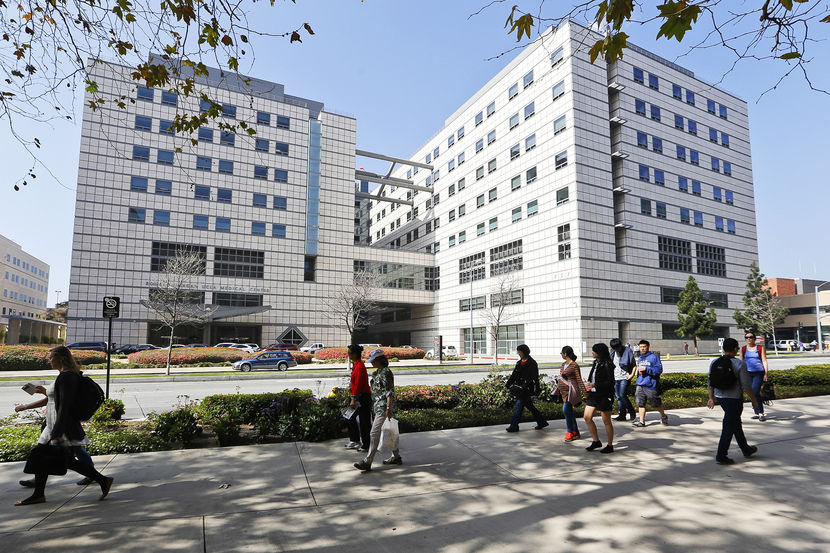 """People walk near the Ronald Reagan UCLA Medical Center in Los Angeles building in Los Angeles, Thursday, Feb. 19, 2015. A """"superbug"""" outbreak suspected in the deaths of two patients at UCLA Medical Center in Los Angeles has raised questions about the adequacy of the procedures for disinfecting a medical instrument used on more than a half-million people in the U.S. every year. (AP Photo/Damian Dovarganes)"""