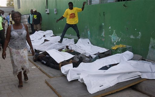 A woman walks away from bodies after failing to find a missing family member among them outside the morgue at the General Hospital in Port-au-Prince, Haiti, Tuesday, Feb. 17, 2015. At least 20 people were killed early Tuesday after a man on top of a musical group's Carnival float was electrocuted, setting off a panic in which dozens of people were trampled, witnesses and officials said. The woman said she would continue looking at a different hospital. (AP Photo/Dieu Nalio Chery)