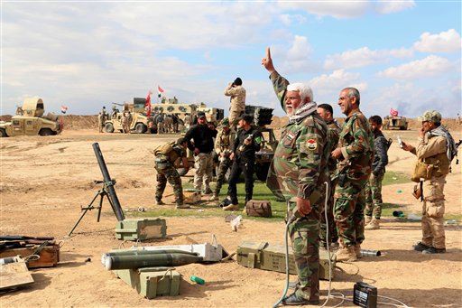 In this Wednesday, March 4, 2015 photo, Iraqi army soldiers and volunteers prepare to launch mortar shells and rockets against Islamic State militant positions outside Tikrit, 80 miles (130 kilometers) north of Baghdad, Iraq. Iranian-backed Shiite militias and Sunni tribes have joined Iraq's military in a major operation to retake Tikrit from the Islamic State group, while the U.S. led coalition has remained on the sidelines. (AP Photo)