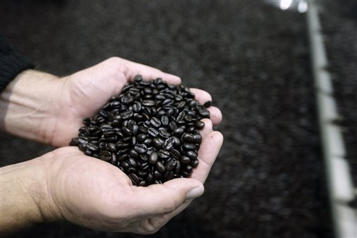 In this photo taken Wednesday, March 4, 2015 John Rogers displays freshly roasted coffee at the Rogers Family Company in Lincoln, Calif.  The  Rogers company is one of several coffee roasters who make single-serve coffee pods for use in the Keurig Green Mountain's single-serve coffee machines. The Rogers Company is one of more than a dozen-coffee-makers and other businesses suing Keurig over what they claim is Keurig's unfair trade efforts to shut out competing single-serve coffee rivals.(AP Photo/Rich Pedroncelli)