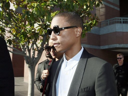 """Pharrell Williams leaves Los Angeles Federal Court after testifying at trial in Los Angeles, Wednesday, March 4, 2015. The Grammy-winning singer Williams says he wasn't trying to copy the late Marvin Gaye's music for the hit song """"Blurred Lines,"""" but he was trying to evoke the feeling of late 1970s tunes. Williams is being sued by Gaye's children, who claim """"Blurred Lines"""" improperly copies their father's hit """"Got to Give it Up."""" Singer Robin Thicke and rapper T.I. are also defendants in the case. (AP Photo/Nick Ut)"""