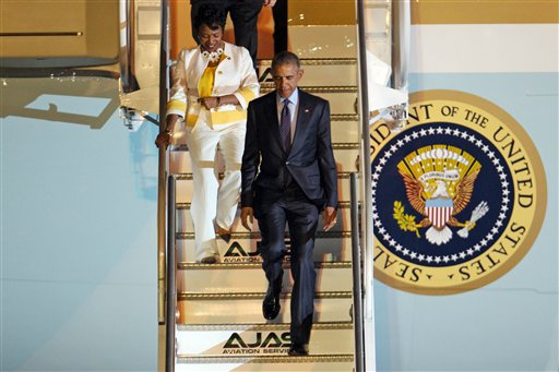 U.S. President Barack Obama, right, accompanied by Rep. Yvette Clarke, D-N,Y, walks down the steps during their arrival on Air Force One, Wednesday, April 8, 2015 at Norman Manley International Airport in Kingston, Jamaica. Obama arrived to Jamaica for a two day visit and will travel to Panama for the Summit of the Americas, April 10-11. (AP Photo/Ricardo Arduengo)