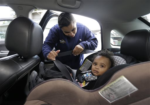 In this Friday, May 15, 2015 photo, Shannon Henderson buckles her son, Justin, 1, into his car seat for the ride to his father's house before she goes to her job as a part-time customer service representative at Wal-Mart in Sacramento, Calif. Henderson is one of an estimated 40 million American workers for who calling in sick is a luxury. If they don't work, they don't get paid. (AP Photo/Rich Pedroncelli)